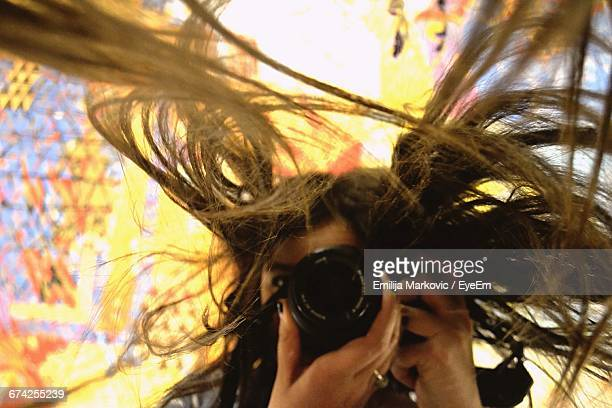 Woman With Tousled Hair Photographing With Camera