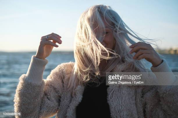 woman with tousled hair standing against sea during sunset - crazy hair stock pictures, royalty-free photos & images