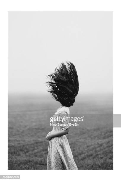woman with tousled hair standing on field during foggy weather - warrig haar stockfoto's en -beelden