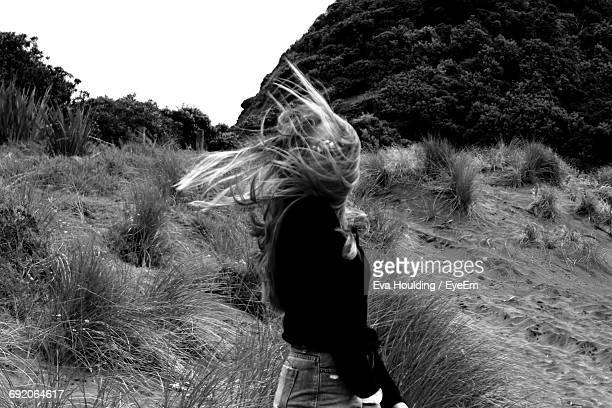 Woman With Tousled Hair Standing On Grassy Field
