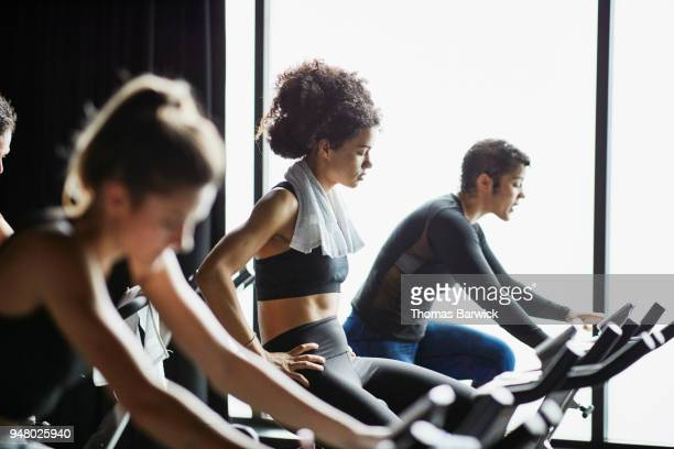 Woman with towel around neck riding stationary bike during cycling class in fitness studio