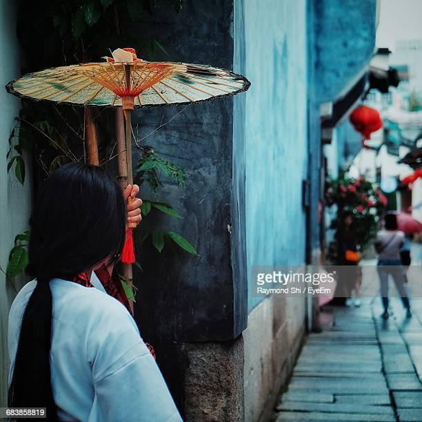 woman with traditional umbrella standing on sidewalk in city - fuzhou stock pictures, royalty-free photos & images