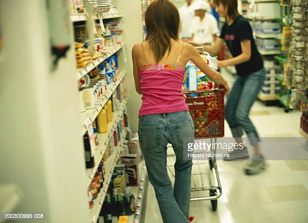 Woman with trolley in supermarket, rear view