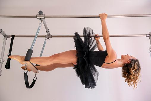 Woman With Tutu Exercising on Pilates Machine - gettyimageskorea