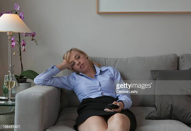 Woman with TV remote relaxing on sofa
