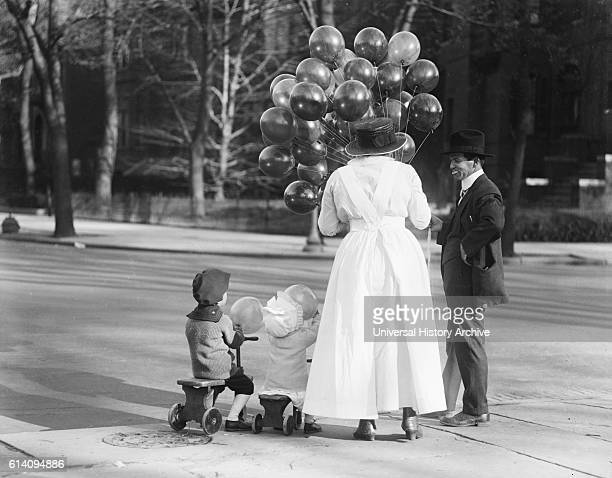 Woman with Two Children Buying Balloons from Vendor USA circa 1919