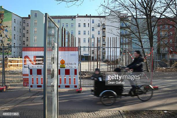A woman with two children rides a bicycle past a glass memorial plaque to Ida Siekmann the first person to die while trying to flee East Berlin over...