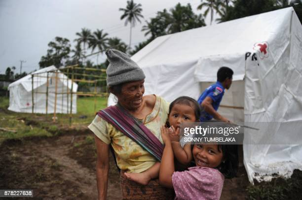 A woman with two children watches as makeshift evacuation structures are built in the Rendang subdistrict of Karangasem Regency as fears of a larger...