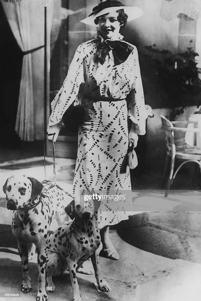 Woman with two dalmatians wearing patterned dress (B&W) : Bildbanksbilder