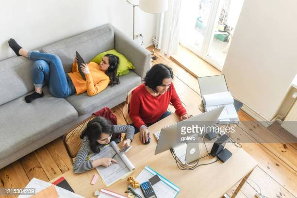 woman with two daughters working at home office in living room - homeschool stock pictures, royalty-free photos & images