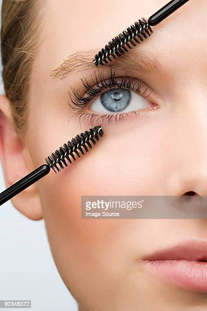 Woman with two mascara brushes
