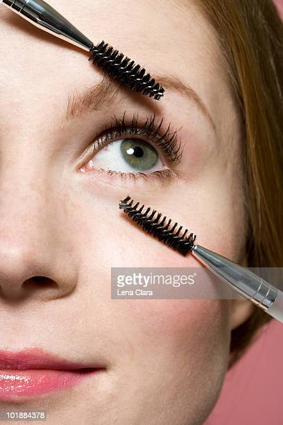 A woman with two mascara wands, extreme close up of face