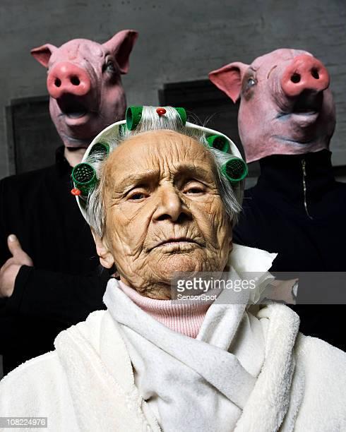 Mulher com dois homens que enveredavam máscaras de Porco