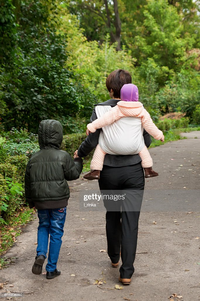 Woman with two siblings in park : Stock Photo