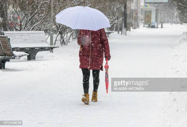 A woman with two umbrellas walks through the snow in downtown Moscow on December 13 2018
