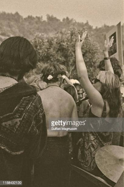 Woman with two-toned hair raising her arms, bare-chested man with flowers in his hair and a cymbal at the 1st Elysian Park Love-In on March 26, 1967...