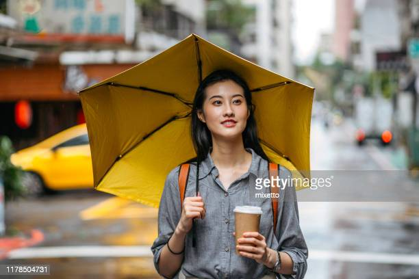 woman with umbrella and coffee on rainy day - umbrella stock pictures, royalty-free photos & images