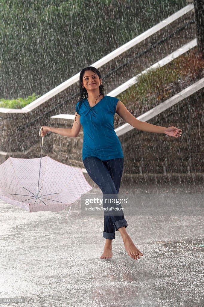 Woman with umbrella enjoying in the rain : Stock Photo