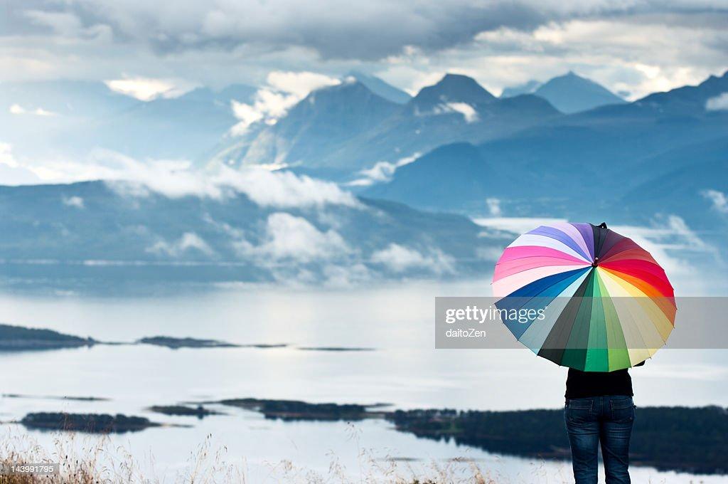 Woman with umbrella enjoying mountain view : Stock Photo