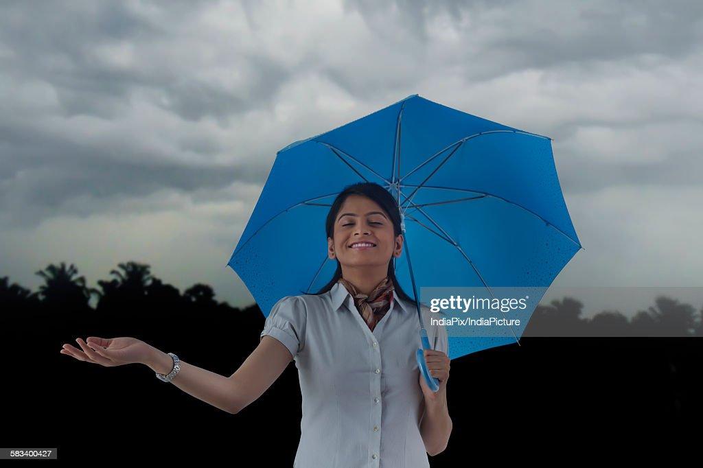 Woman with umbrella enjoying the rain : Stock Photo