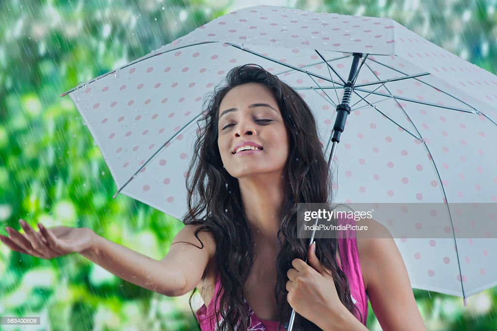 Woman with umbrella enjoying the rain : Stock Photo