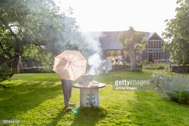 woman with umbrella having barbecue in garden - funny bbq stock pictures, royalty-free photos & images