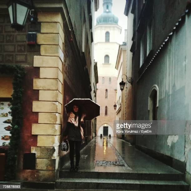 woman with umbrella in city alley - black alley stock photos and pictures