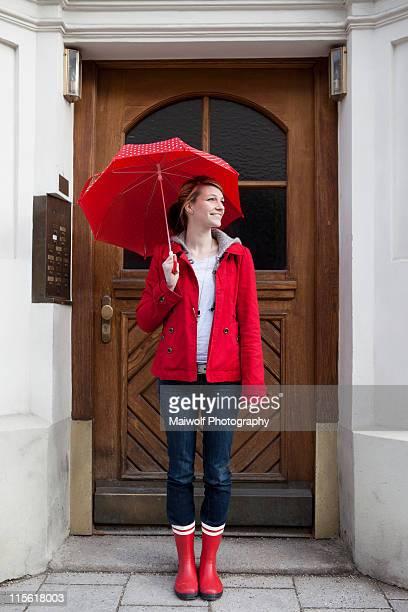 woman with umbrella in front of house - regenschirm stock-fotos und bilder
