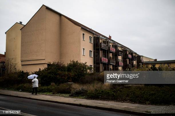 A woman with umbrella is pictured in front of residences on December 08 2019 in Brandenburg Germany