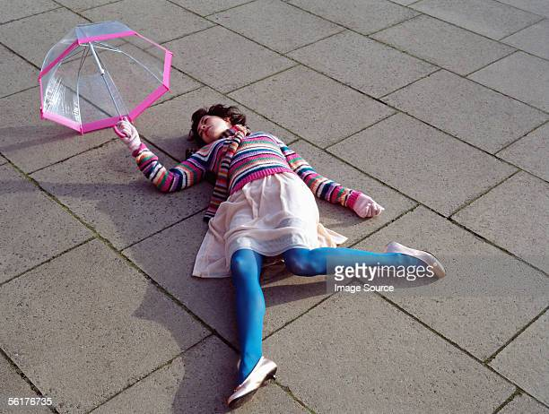 Woman with umbrella lying down