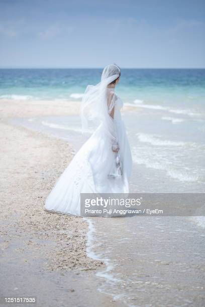 woman with umbrella on beach against sky - strapless evening gown stock pictures, royalty-free photos & images
