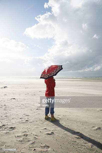 Woman with umbrella on the beach, wind, thunder cloud, Langeoog island, East Frisian Islands, North Sea, Germany, Europe