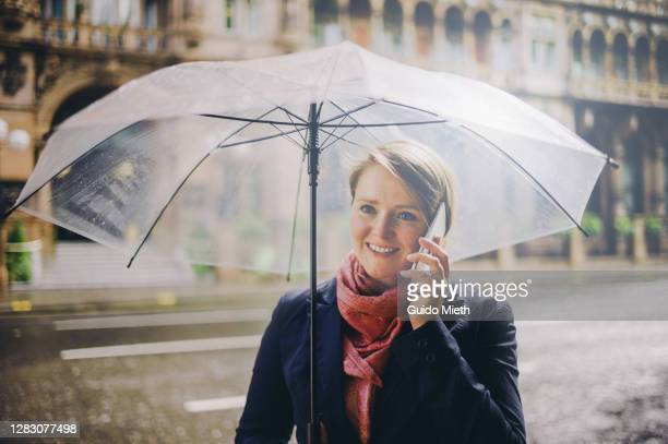 woman with umbrella phoning in the rain. - northern european descent stock pictures, royalty-free photos & images