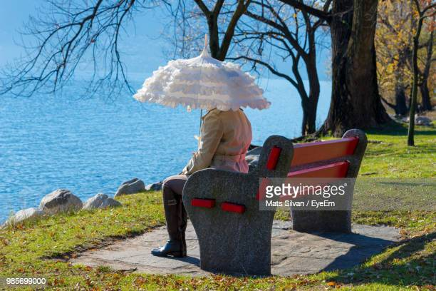 Woman With Umbrella Sitting By Lake On Bench