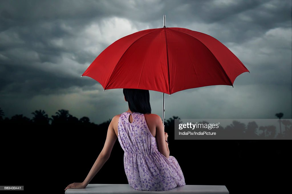 Woman with umbrella sitting : Stock Photo