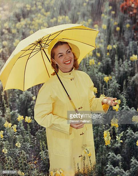 woman with umbrella standing in flowers - vintage raincoat stock photos and pictures