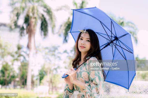 woman with umbrella standing in rain - rainy season stock pictures, royalty-free photos & images