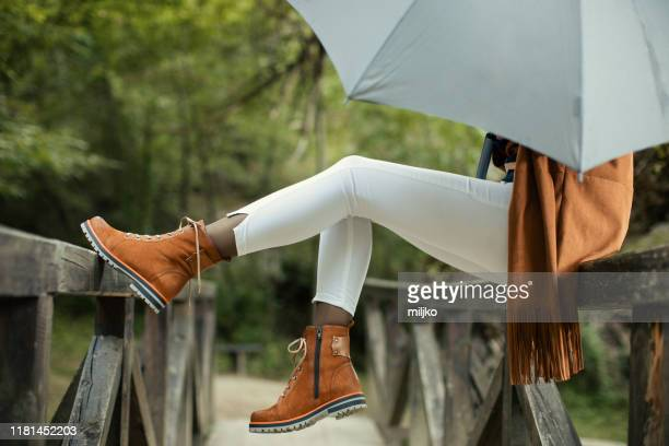 woman with umbrella standing on bridge - boot stock pictures, royalty-free photos & images