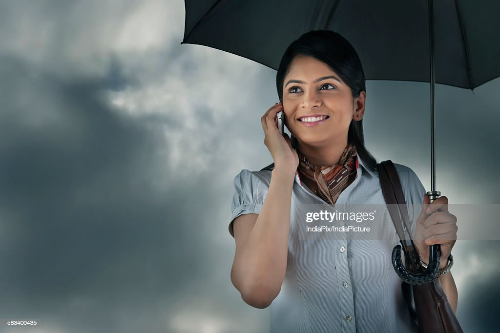 Woman with umbrella talking on mobile phone : Stock Photo