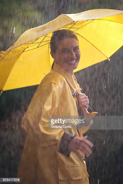 woman with umbrella walking in pouring rain - vintage raincoat stock photos and pictures