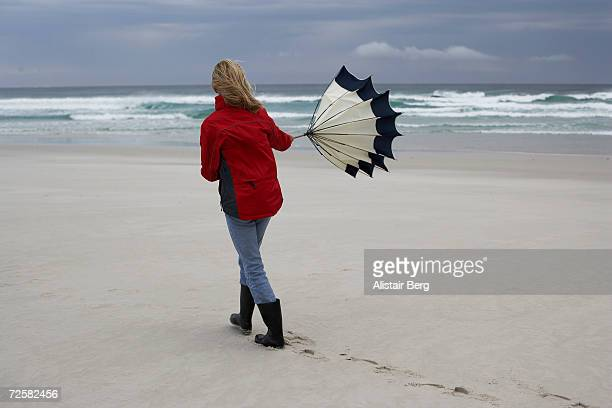 Woman with umbrella walking on beach