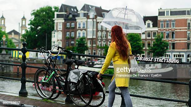 Woman With Umbrella Walking On Footbridge Over Canal Against Buildings In City