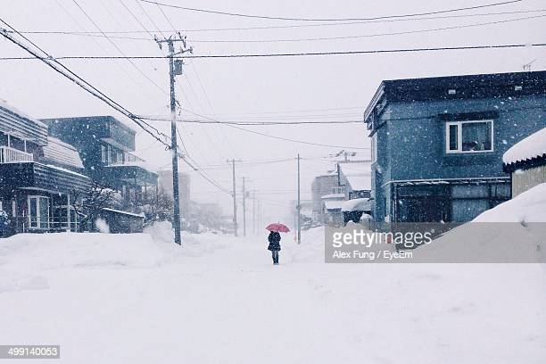 Woman with umbrella walking on snowy street