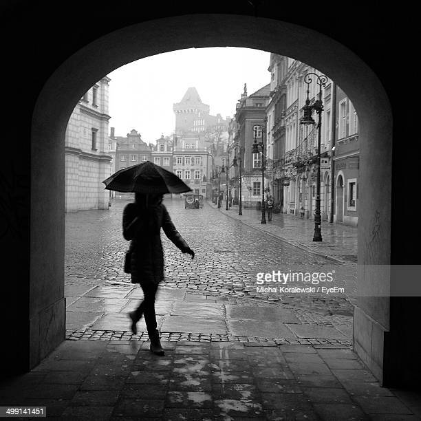 Woman with umbrella walking on street against buildings