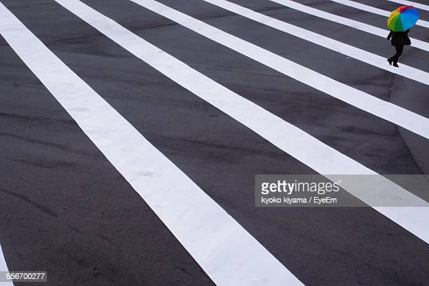 Woman With Umbrella Walking On Zebra Crossing