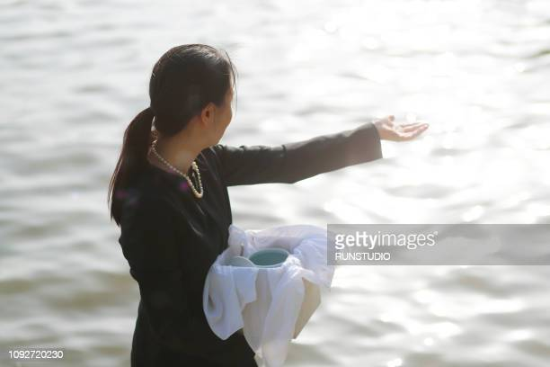 woman with urn spreading ashes - crematorium stock pictures, royalty-free photos & images