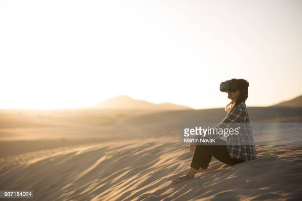 Woman with virtual reality glasses in desert