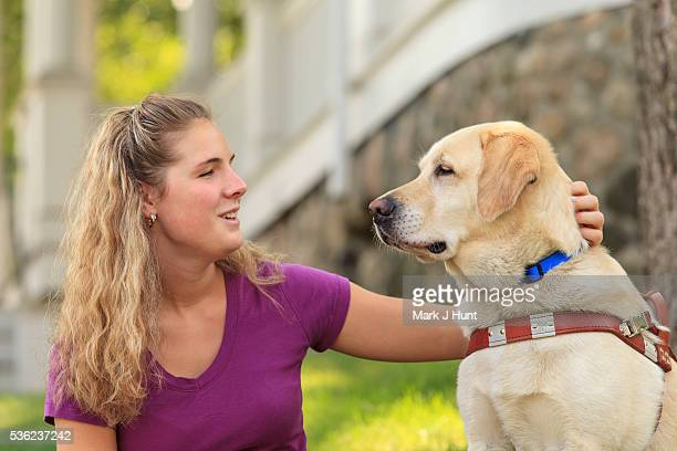 Woman with visual impairment petting her service dog