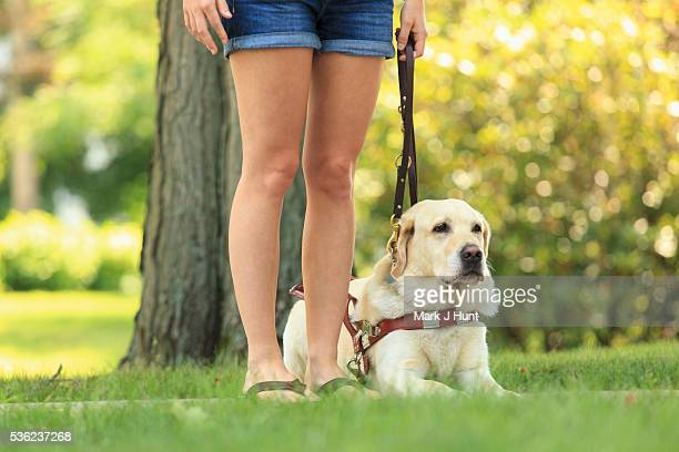 Woman with visual impairment with her sitting service dog