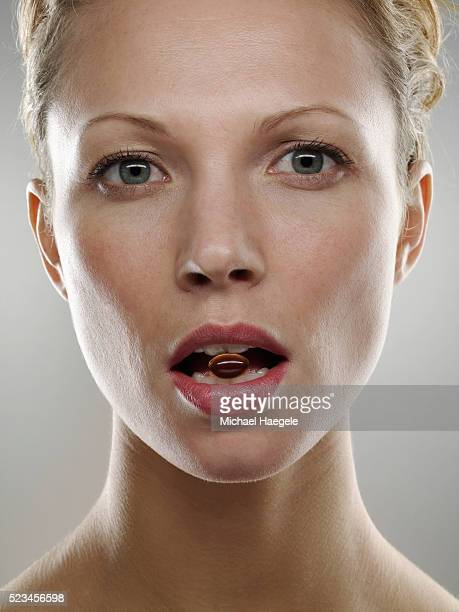 Woman with Vitamin in Mouth